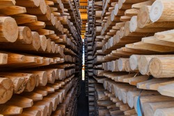 Piles of wooden boards in the sawmill, planking. Warehouse for sawing boards on a sawmill outdoors. Wood timber stack of wooden blanks construction material. Lumber Industry.