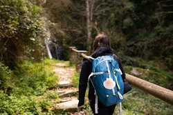 Pilgrim brunette woman, doing the Camino de Santiago, in a forest, with a blue backpack and a shell, with a black jacket, looking at a waterfall. Lifestyle concept. Hike, way of st james