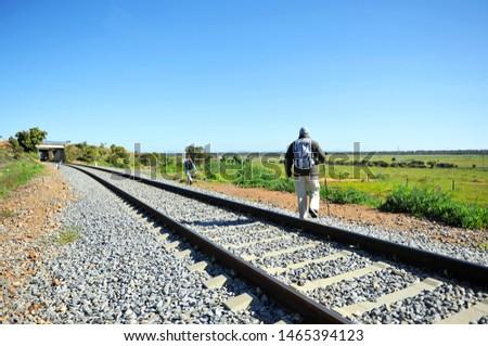 Pilgrim crossing the train tracks on the Via de la Plata between Torremejias and Mérida, province of Badajoz, Spain. Via de la Plata is the Camino de Santiago from Seville to Santiago de Compostela