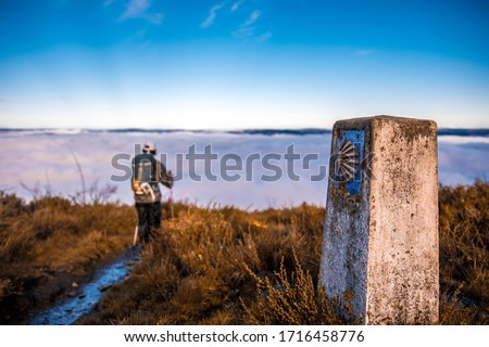 Pilgrim walking in Camino de Santiago, over a sea of clouds in the middle of the nature. We can see the icon of the shell. Foto d'archivio ©
