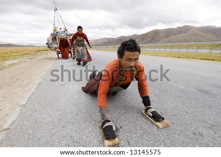 pilgrimaging Tibetan on the road. they keep on prostrating themselves, touching ground by forehead. the whole trip from home to lhasa will take 18 months(1500 miles).
