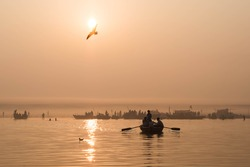 Pilgrims approaching the East bank of the sacred Ganges river by boat at sunrise in Varanasi, Uttar Pradesh, India.