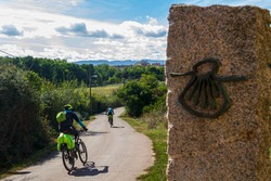 Pilgrims cyclists on the route of the Camino de Santiago (Way of Saint James) passing next to the scallop shell that marks the way