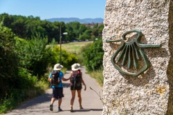 Pilgrims on the route of the Camino de Santiago (Way of Saint James) passing next to the scallop shell that marks the way