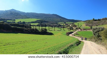 Shutterstock Pilgrims walking through endless green fields under the sun of a beautiful spring morning, Camino de Santiago, Navarra, Spain.