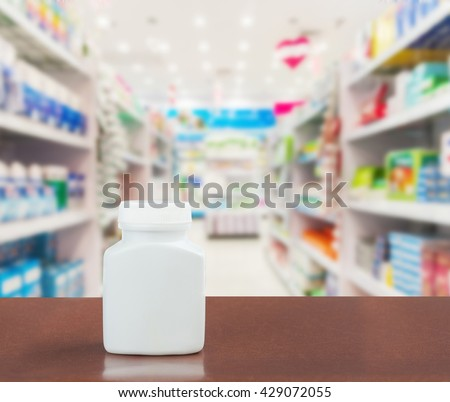 Pill bottle on table top on blurred pharmacy, Pharmacy in shopping mall, Pharmacy in shopping center, Shopping drug and pill at pharmacy in holiday