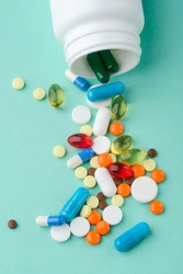 Pill bottle, scattered vitamins and supplements, close-up. Light pastel surface. Medicine and pharmacists.