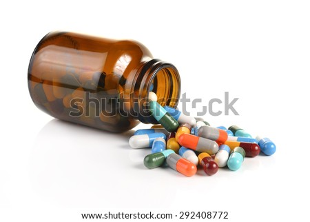 Pill bottle spilling pills on to surface isolated on a white background.