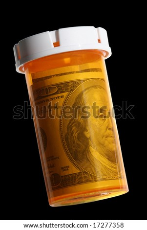 Pill Bottle Stuffed with Money: $100 dollar bill isolated on black background
