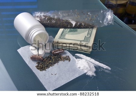 pill bottle with marijuana, cocaine, weed and drug money on a glass table
