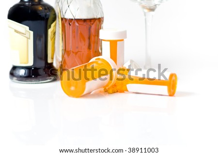 Pill bottles spilling pills out, with liquor bottles and a wine glass in the background, isolated on white.