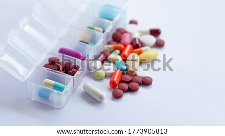 Pill box daily take a medicine, with colorful of pills, tablets, and capsules. Drugs use for treatment and cure the disease. Medication in medical clinic isolated in white background, has copy space.