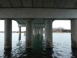 Pillars under the bridge looking over the water in Sag Harbor, New York