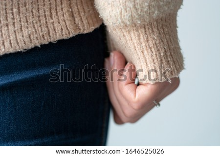 Photo of  Pilled sweater. Closeup woman wearing a old used sweater with lint (pilling).