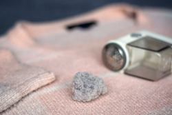 Pilled sweater. Handheld electric fabric shaver fuzz remover device machine for removing fuzz, lint and pills on clothes.
