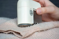 Pilled sweater. Woman hand using handheld electric fabric shaver fuzz remover device machine for removing fuzz, lint and pills (pilling) on clothes