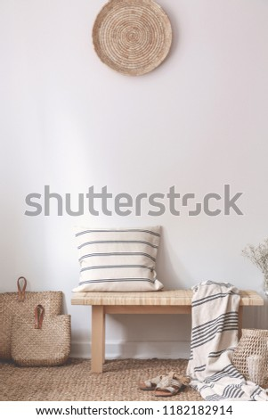 Pillow and blanket on wooden bench next to bags in natural white living room interior. Real photo