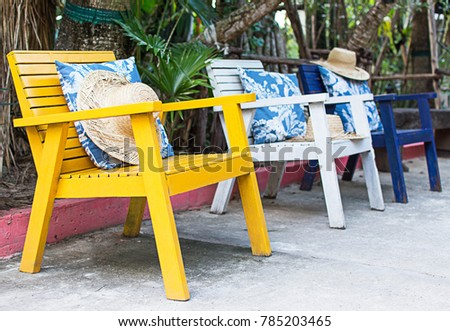 Pillow and hat on the chairs in the summer, focus of yellow chair.