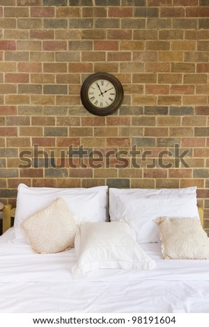 Pillows and bed in bedroom with brick wall