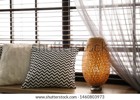 Pillows and lamp on windowsill in room. Stylish interior elements