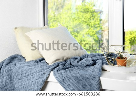 Pillows and warm knitted plaid on a window sill