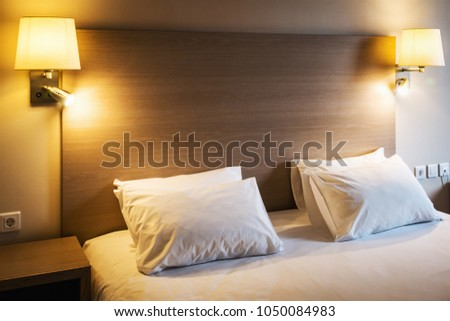 Pillows on a large king-size bed. Concept on preparation of the bed in a hotel room or at home #1050084983
