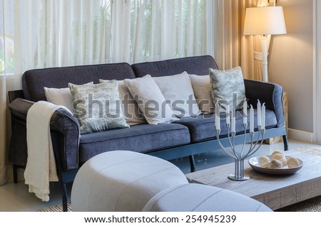 pillows on blue sofa with lamp and candle holders on wooden table in living room #254945239