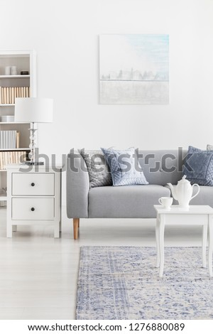 Pillows on grey couch next to lamp on cabinet in elegant living room interior with poster. Real photo