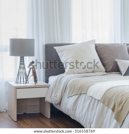 pillows on modern bed with grey lamp on wooden table side in modern bedroom