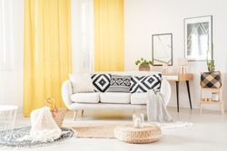 Pillows with geometric pattern lying on a white sofa in cozy living room with yellow curtains