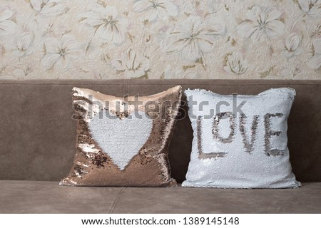 Pillows with sequins. White and golden pillows lie on a brown sofa. Golden pillow with a white heart, white pillow with the inscription Love. Place for text