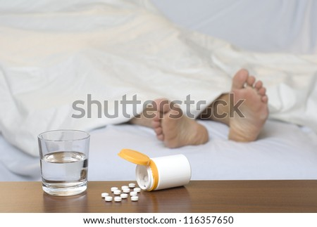 Pills and a glass of water on the table. Sleeping person in the background.