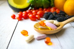 Pills and capsules in wooden spoon with fresh fruits.Multivitamins and supplement from fruits concept.