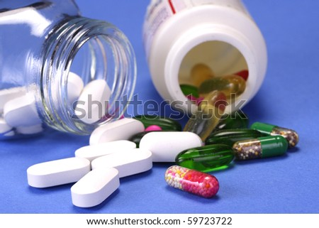 Pills and capsules poured out of botles