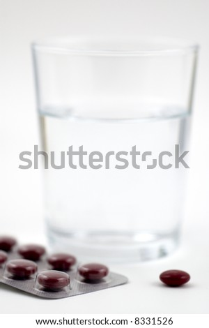 pills and glass of water, shallow depth of field