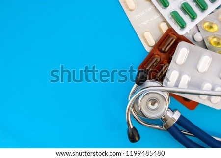 Pills and medications in blister packs and stethoscope on blue background occupy half of photo, in second half - empty space for titles. Concept photo of pharmacological treatment of diseases