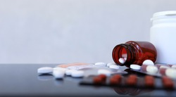 Pills and medicine bottles on glass, medical concept