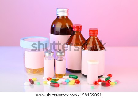 Pills and medicine bottles on pink background - stock photo