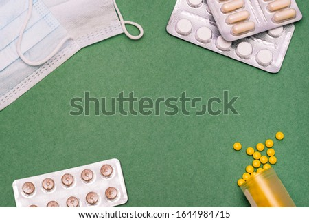 Pills and protective masks on a green background. Medicines for flu and colds. Medicine and health symbols.