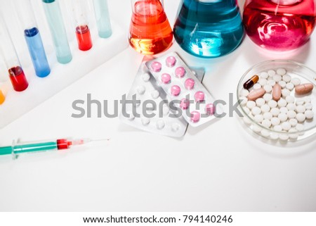 pills and syringe. injection and vaccination. drug discovery, pharmacology and biotechnology concept. science and medical research background with copy space.