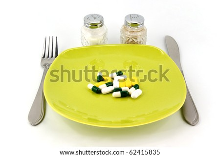 pills as dinner on plate on white background
