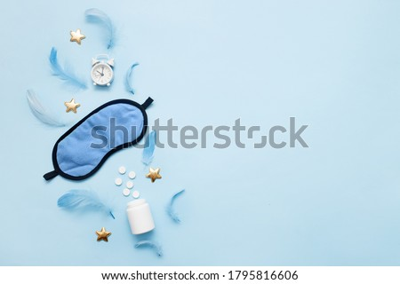 Pills, bottle, sleeping mask and white alarm clock with stars on blue pastel background. Concept Insomnia, sleep problems, time to take pills and treatment. Top view, flat lay, copy space. Foto stock ©