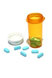 Pills in a pill bottle. Isolated on white. Room for text. Blue pills spilling out of a plastic pill bottle on a white background.