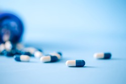 pills in capsules blue and white scattered on the table from a jar on a blue background