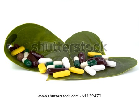 pills in green leaf on white background