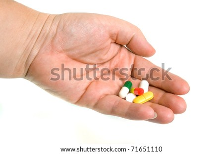 pills in palm on white background