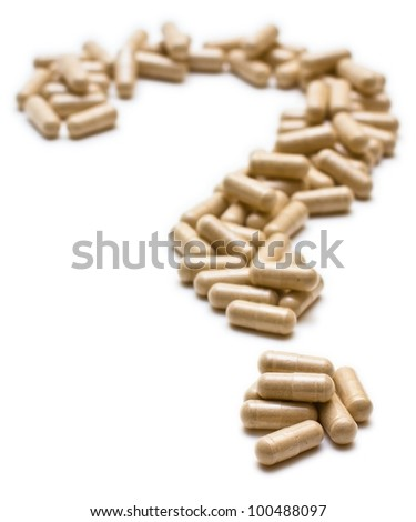Pills in the shape of a question mark, concept for medical / healthcare. Shallow depth-of-field image with focus on the nearest capsule. Isolated over white background.