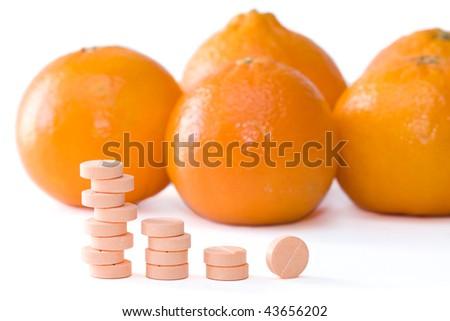 Pills of vitamin C on a background of orange