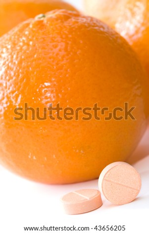 Pills of vitamin C on a background of orange