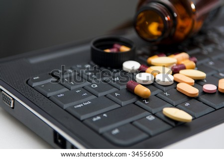 Pills on a laptop, work pressure concept.